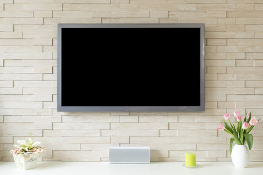 Blank modern flat screen TV at the white brick wall with copy space