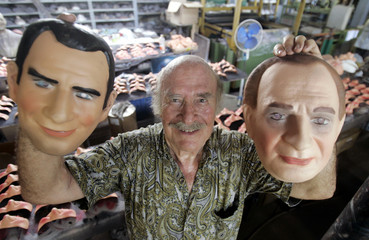 Valles holds up masks of King Juan Carlos and Crown Prince Felipe in Rio de Janeiro