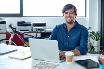 Portrait of male graphic designer working on laptop