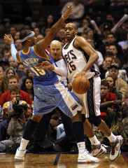 New Jersey Nets Carter guarded by Denver Nuggets Anthony in their NBA basketball game in East Rutherford