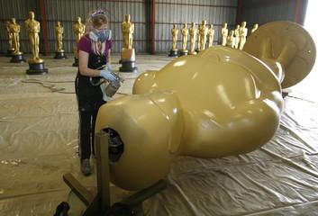 Scenic artist Dena D'Angelo sprays a fresh coat of paint on a large Oscar statue near Los Angeles