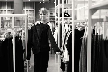 Junge Frau beim Shopping in einem Modehaus mit einem Jacket
