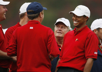 Woods and Mickelson of U.S. laugh after first round at the President's Cup golf tournament