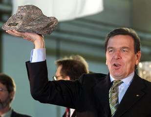 German Chancellor Gerhard Schroeder lifts a granite stone he received as a present after a speech in..