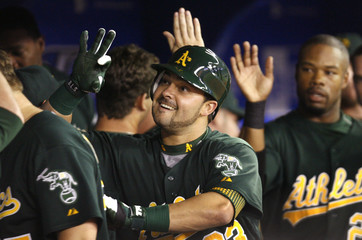 Oakland Athletics' Nick Swisher is congratulated by teammates after hitting a home run against the Toronto Blue Jays in Toronto