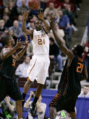 Texas' Mason passes between Miami's King and Collins during the first half of their second round NCAA men's basketball tournament game in Little Rock