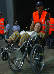 A Lebanese-Swiss woman is assisted by Swiss officials to board a Greek warship at the port of Beirut,