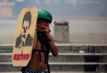 An opposition supporters uses a home made shield with a painting resembling Venezuela's President Nicolas Maduro wiht a clown nose, in Caracas