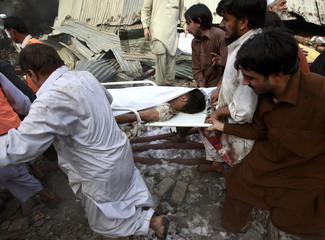 Men carry bodies of victims to ambulances at the scene of a car-bomb explosion in Peshawar
