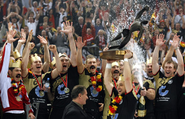 Germany's players holds the Handball World Cup trophy as they celebrate their victory in the final mach against Poland in Cologne