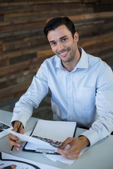 Male graphic designer holding photos in office