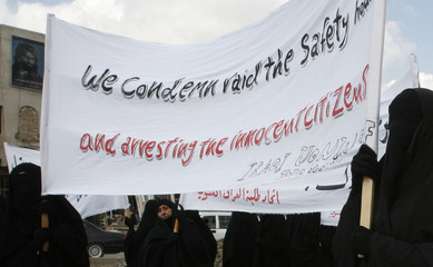 Women display a banner during a protest after Friday prayers in Baghdad's Sadr City