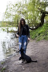 Young beautiful girl with a black dog near a lake