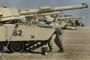 US ARMY SOLDIERS RESTS ON HIS TANK IN THE DESERT OUTSIDE KUWAIT CITY.