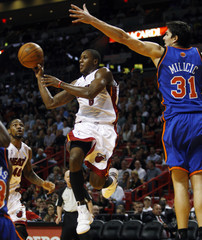 Miami Heat New Mario Chalmers jumps as he passes the ball against New York Knicks Darko Milicic during their NBA opening game in Miami