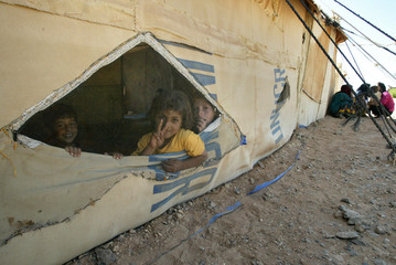 Kurdish children from Iran's Kurdish minority looks out from their tent at Ruweished