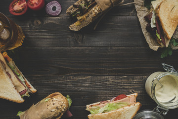 Fresh delicious sandwiches on the wooden dark table with copy space. Top view
