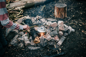 Male hand picking up hot kettle from campfire with branch.