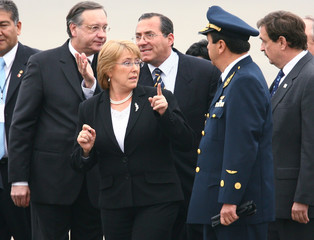 Chile's President Michelle Bachelet is surrounded by protocol officers after arriving in Lima