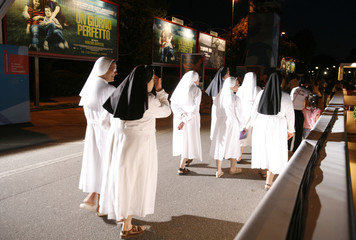 Nuns walk in front of the Cinema Palace in Venice