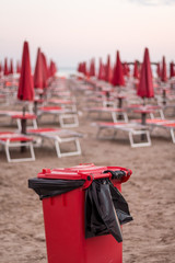 Red trash can and umbrellas on beach