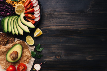 Healthy vegan food concept. Healthy food with vegetables and whole wheat bread on the wooden table top view. Copy space Wall mural