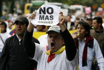 """A demonstrator protests holding a banner that reads """"No more Chavez"""" on a central street in Bogota"""