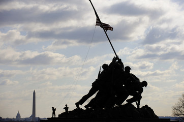 A pair of US Marines attempt to untangle a wind-blown flag before a ceremony in honor the 64th anniversary of the raising of the US flag on the island of Iwo Jima during World War II, at the Marine Corps War Memorial in Arlington, Virginia