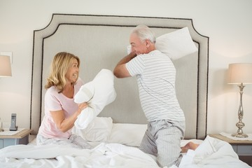 Laughing couple having pillow fight on bed