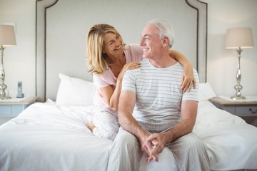 Smiling woman embracing man on bed