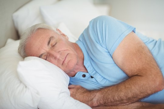 Senior man sleeping on bed