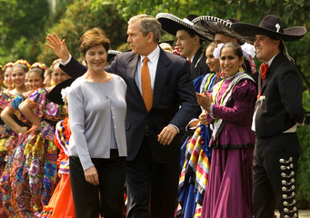 U.S. President George W. Bush waves to supporters as he and his wife Laura walk past a line of Mexic..