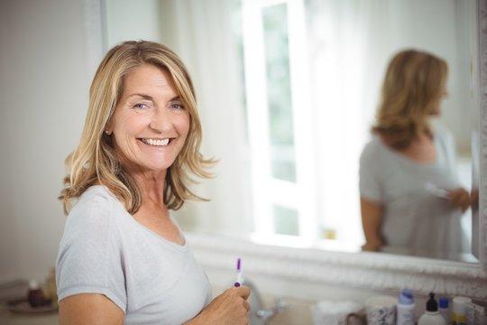 Portrait of senior woman holding toothbrush in bathroom
