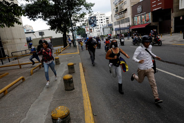 Opposition supporters run away while rallying against Venezuelan President Nicolas Maduro in Caracas