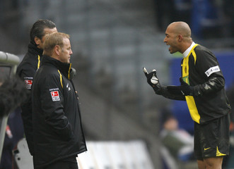 Dortmund's Dede talks to his coach Roeber as he leaves the pitch after receiving a red card during their German Bundesliga first division soccer match against Hamburg SV in Hamburg