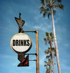 aged and worn vintage photo of drinks sign on beach with palm trees