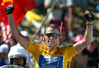 US Postal team rider Lance Armstrong (R) of the USA celebrates as he crosses the finish line to win ..