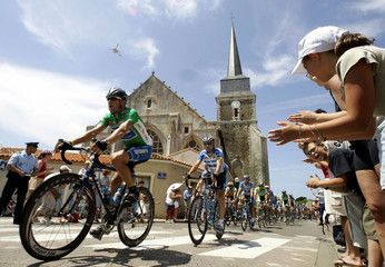Discover Channel team rider Lance Armstrong (L) of the U.S. is cheered on by spectators as he passes..