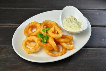 Fried onion rings. Fast food on hardwood
