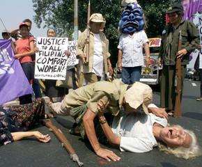 """A FILIPINO """"COMFORT WOMAN"""" SCREAMS AS A FELLOW PROTESTOR PRETENDS TORAPE HER IN MANILA."""