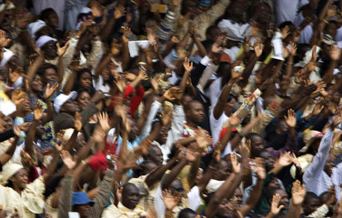 The crowd waves at Pope Benedict XVI as he arrives at the main stadium to lead a mass in Cameroon's capital Yaounde