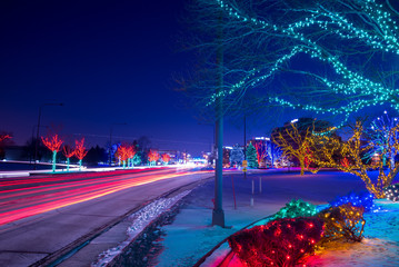 Cityscape night with car's stoplight trails and Christmas lights