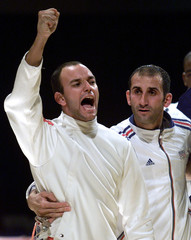 Fencer Hugues Obry (L) of France punches the air as he stands next to epee teammate Jean-Francois Di..