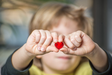 Close up of a boy's hands holding a red heart