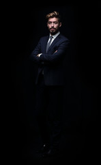 Portrait of young and handsome business man isolated on black