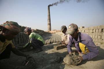 Workers prepare soil to make bricks in a brick field on the outskirts of Dhaka