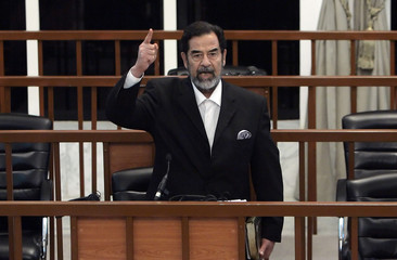 Former Iraqi President Saddam Hussein yells at court as he receives verdict during trial in Baghdad