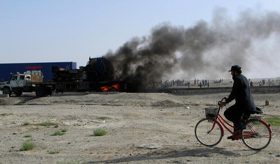 A man rides his bicycle past burning vehicles along the Chaman Pakistan-Afghanistan border