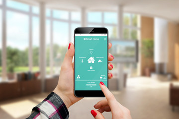 Female hand holding smartphone with home control application, home interior in background