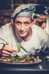 Food concept. Preparing traditional italian pizza. Young handsome chef in white uniform and gray hat decorate ready dish with green rucola herbs in interior of modern restaurant kitchen. Ready to eat.